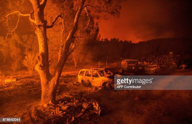Fire illuminates the scene where the remains of a burned out property are seen near the town of Mariposa California on July 18 2017 California has...