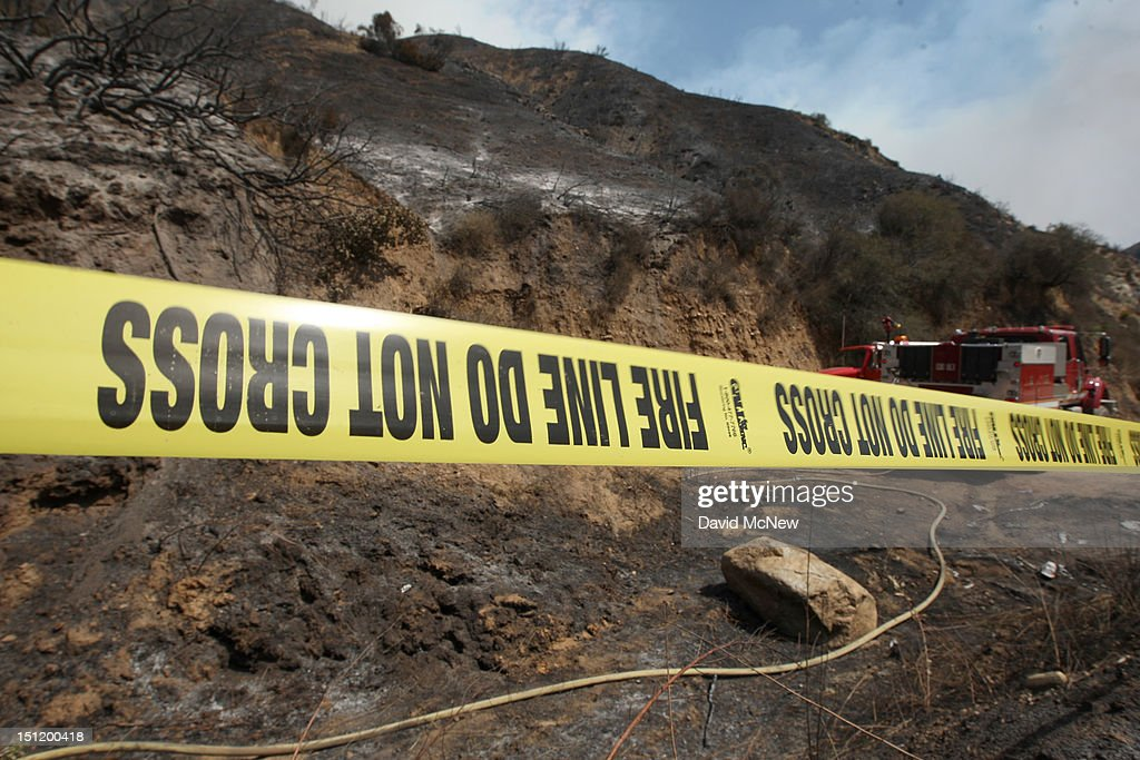Fire investigator's tape marks the spot they believe could be the origin of the Williams fire in the Angeles National Forest on September 3, 2012 north of Glendora, California. The fire began late September 2, putting an early end to Labor Day weekend camping and hiking for vacationers, who were evacuated from the area as it spread to more than 4,000 acres in size. Three hundred to 400 firefighters are on the ground, with more expected to arrive soon, and at least six air tankers and eight helicopters have been called in.