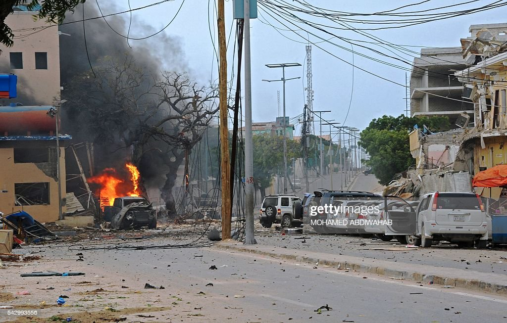 Fire is seen at the scene of a car bomb attack claimed by Al-Qaeda-affiliated Shabaab militants which killed at least 5 people, on the Naasa Hablood hotel in Mogadishu on June 25, 2016. The hotel in southern Mogadishu is often used by politicians and members of the Somali diaspora visiting the city. The attack came just three weeks after another assault quickly claimed by the Al-Qaeda-linked Shabaab group on the city's Ambassador hotel left 10 dead including two lawmakers when a huge car bomb ripped the front off the six-storey building. / AFP / MOHAMED