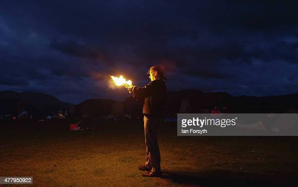 Fire jugglers entertain visitors at sunrise at the ancient stone circle at Castlerigg as they celebrate dawn on the the summer solstice on June 21...