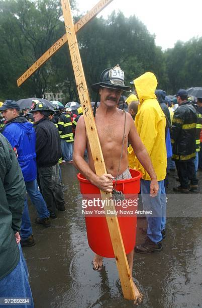 Fire Lt Rich Patterson of the Bronx slogs through the mud wearing only a plastic barrel to make a point about his wages during the Uniformed...