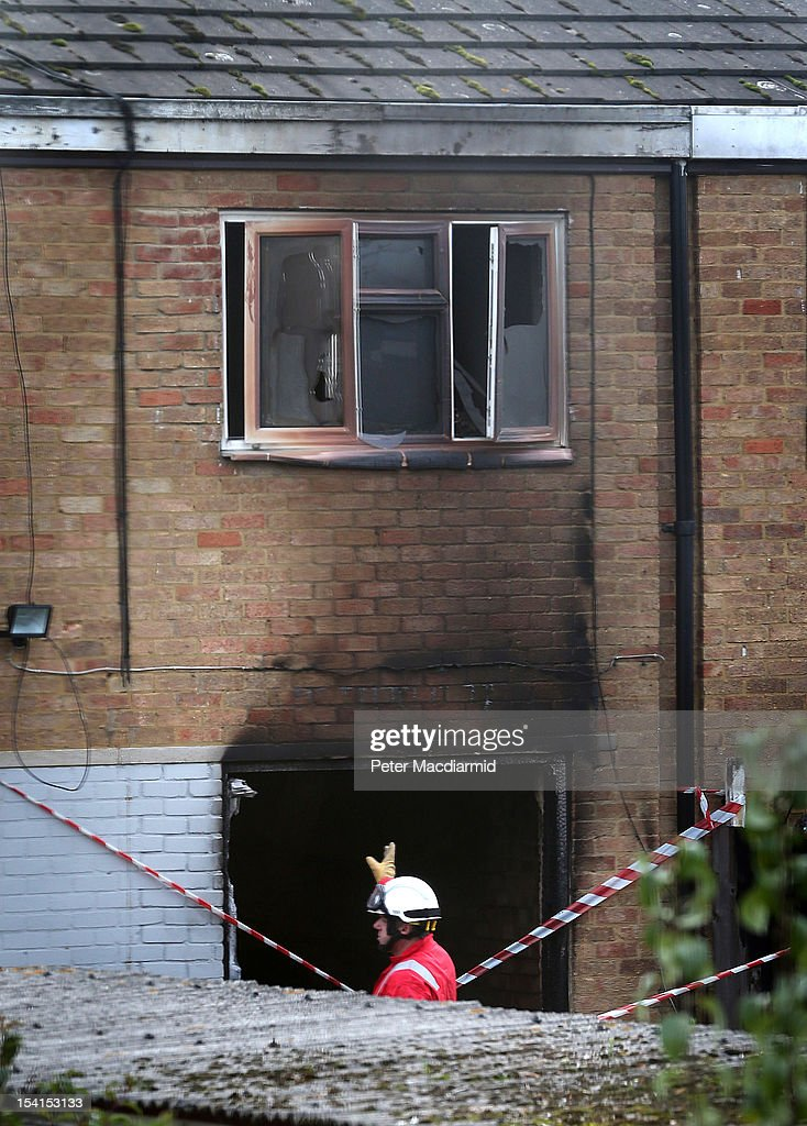 A fire officer inspects the back of a fire damaged house where five people died on October 15, 2012 in Harlow, England. A woman and four children have died and another three are in hospital after a fire in a house on an estate near Harlow in Essex.