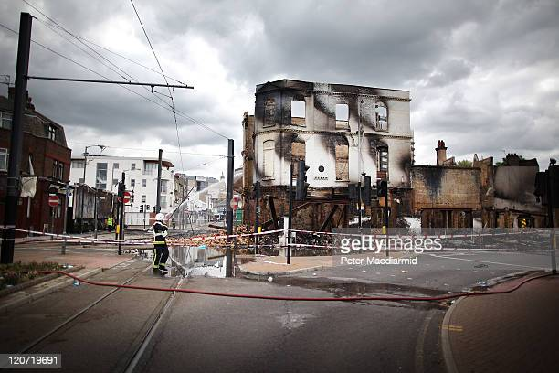 A fire officer stands by the burnt remains of Reeves Corner furniture store on August 9 2011 in Croydon England Emergency services have been cleaning...