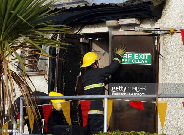 Fire officers attend to a door at the St Johns GAA club near Castlewellan in Co Down where a fire this morning destroyed priceless memorabilia in the...