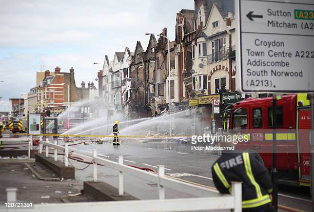 Fire officers damp down smouldering buildings on London Road on August 9 2011 in Croydon England Emergency services have been cleaning up after a...