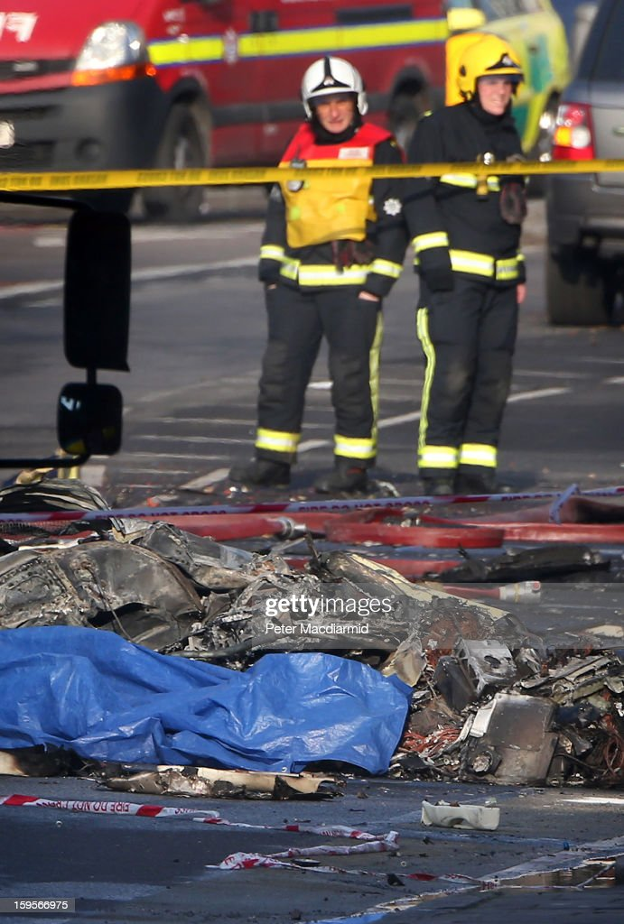 Fire officers stand near the remains of a helicopter that crashed in Vauxhall, on January 16, 2013 in London, England. According to reports, a helicopter hit a crane on St Georges Wharf Tower before plunging into the road below during the morning rush hour.