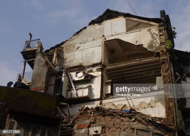 Fire Officials inspecting a part of Ramchandra Building collapsed on Sunday night opposite Gokuldas Tejpal Hospital on Lokmanya Tilak Marg near Metro...