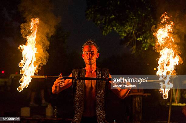 A fire performer dazzles the crowd at an open-air market by spinning a flaming baton.