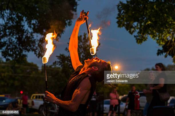 A fire performer dazzles the crowd at an open-air market by swallowing a flaming baton.
