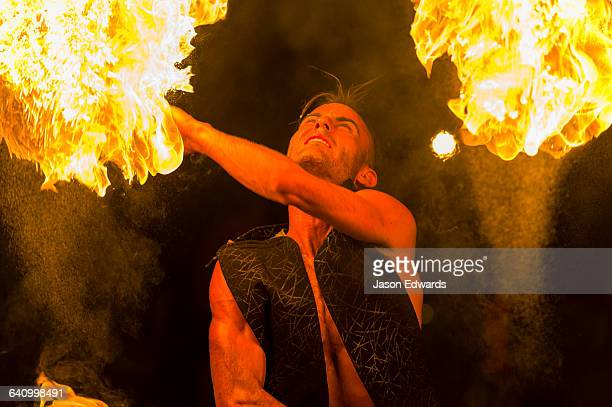 A fire performer dazzles the crowd at an open-air market by throwing a flaming baton.