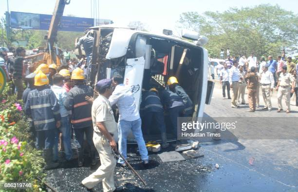 Fire personnel Police personnel and bystander helping in rescuing passenger after a Private bus transporting people for reception from Malad to...