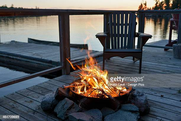 Fire Pit On A Wooden Dock On A Lake At Sunset