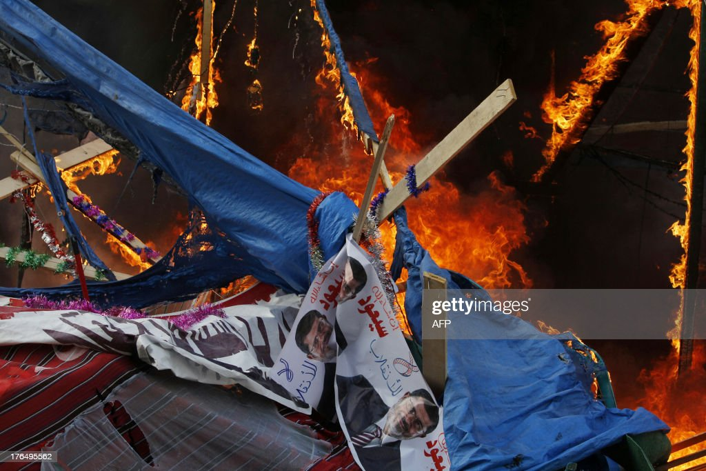 A fire rages in a protest tent as Egyptian security forces moved in to disperse supporters of Egypt's ousted president Mohamed Morsi by force in a...