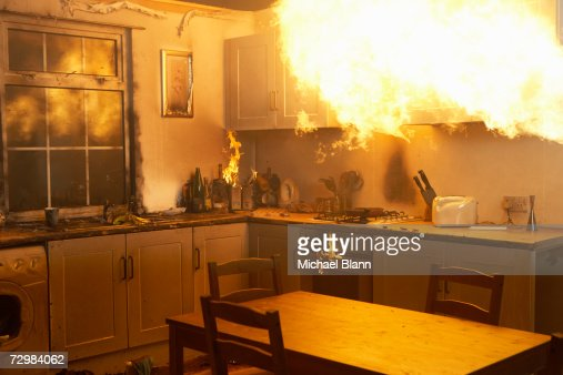 Fire raging in domestic kitchen at night : Stock Photo