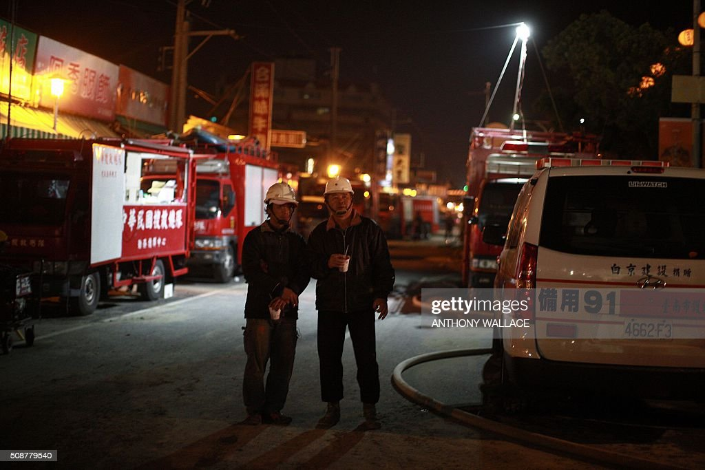 Fire rescue workers hold hot drinks as they look towards the site of a collapsed building in the southern Taiwanese city of Tainan on February 6, 2016 following a strong 6.4-magnitude earthquake. More than 250 people have been rescued from the Wei-kuan apartment complex in the southern city of Tainan since the quake hit at 4:00 am Saturday, killing 14 people and toppling four blocks of around 100 homes in total. WALLACE