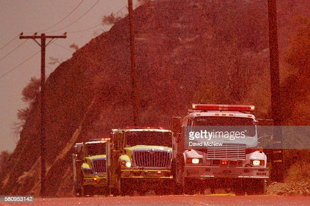 Fire retardant dropped by a helicopter rains down on firetrucks in Placerita Canyon at the Sand Fire on July 25 2016 in Santa Clarita California...