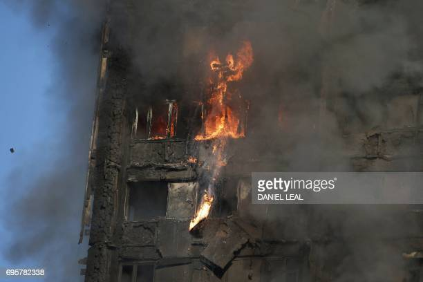 TOPSHOT Fire rips through Grenfell Tower as firefighters attempt to control a huge blaze on June 14 2017 in west London The massive fire ripped...