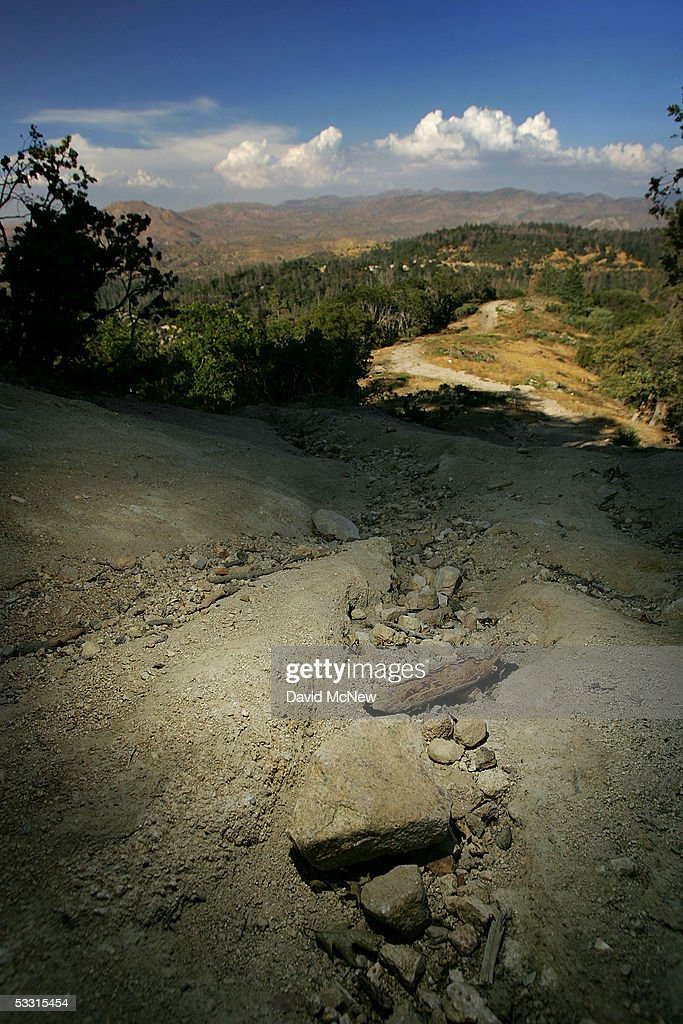 A fire road is seen eroded and clogged with rocks after a winter of record rains, as thunder clouds build in the distance bringing the threat of lightning-caused wildfires on August 1, 2005 near Lake Arrowhead, California. Last winter was one of the wettest on record, dropping 90 inches of rain in some southern California mountain areas and creating the thickest vegetation growth in memory, and damaging more than 2,000 miles of fire access roads used to protect 2.3 million acres of forests. In addition to the many thousands of trees killed by a massive pine beetle infestation, newly grown vegetation is drying up under triple-digit temperatures and raising fears of a repeat of the devastating fire season of 2003. President Bush signed an emergency funding bill in May allocating $25 million to fix roads in southern California?s national forests but Congress has acted slower than expected in providing the money so some of the repairs might not be done until October.
