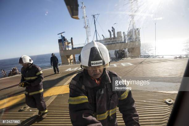 Fire safety personnel greet visitors on the helicopter landing pad aboard the Mafuta diamond mining vessel operated by Debmarine Namibia a joint...