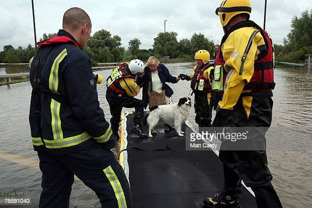 Fire Service rescue boat helps an elderly woman and her dog as water floods areas of Tewkesbury Gloucestershire following the torrential rain in the...