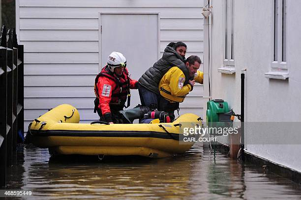 Fire services personnel assist in the evacuation of residents in Wraysbury west of London on February 11 2014 In normally tranquil Wraysbury...
