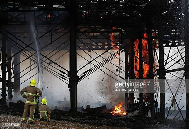 Fire services personnel work to douse flames after a fire ripped through the pier in Eastbourne on July 30 2014 The roof of Eastbourne's pier which...