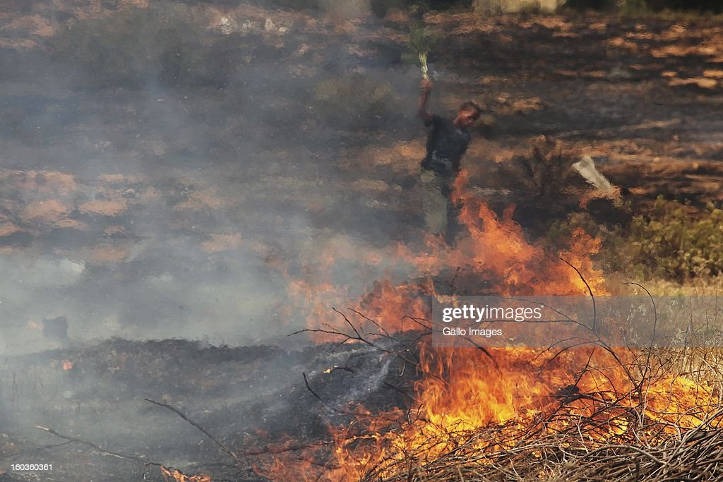 A fire smoulders at De Hoop farm on January 29, 2013, in Paarl, South Africa. No firemen were present as the veld fire swept through the entire Boland region in the Western Cape.