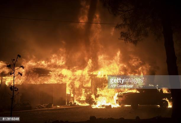 TOPSHOT A fire tornado appears above a burning house during the Wall fire in Oroville California on July 08 2017 The first major wildfires after the...