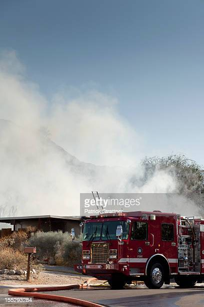 A fire truck next to a burning house in a suburb