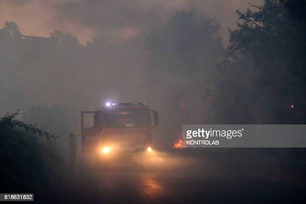 A fire truck shrouded in smoke during a vast fire that threatened inhabited areas between Naples and Campi Flegrei throughout the day