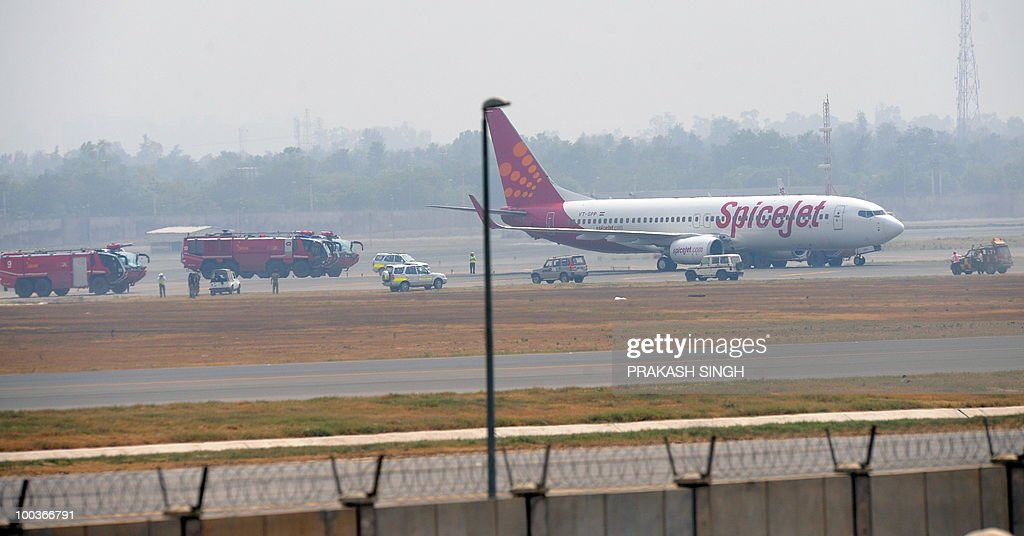 Fire trucks and Indian airport security vehicles surround a Spicejet Boeing 737-800 aircraft which made an emergency landing at Indira Gandhi International airport in New Delhi on May 24, 2010. An Indian passenger jet carrying 184 people on board made an emergency landing in New Delhi's main airport May 24 after the aircrafy suffered a tyre-burst while taking off. The Srinagar-bound Boeing 737-800 aircraft aborted a flight to Srinagar city in Kashmir and returned to the Indira Gandhi Airport which declared a 'full emergency' before it was allowed to land, officials said. AFP PHOTO/ Prakash SINGH