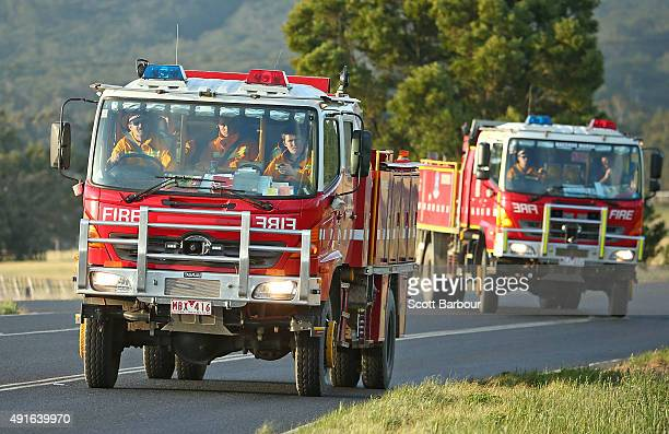 Fire trucks drive towards a bushfire in Lancefield Victoria on October 7 2015 near Melbourne Australia Victorian fire crews have been battling to...