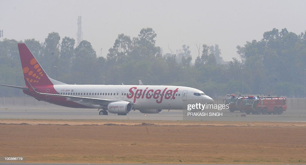 Fire trucks surround a Spicejet Boeing 737-800 aircraft which made an emergency landing at Indira Gandhi International airport in New Delhi on May 24, 2010. An Indian passenger jet carrying 184 people on board made an emergency landing in New Delhi's main airport May 24 after the aircrafy suffered a tyre-burst while taking off. The Srinagar-bound Boeing 737-800 aircraft aborted a flight to Srinagar city in Kashmir and returned to the Indira Gandhi Airport which declared a 'full emergency' before it was allowed to land, officials said. AFP PHOTO/ Prakash SINGH