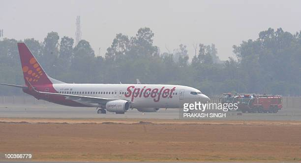 Fire trucks surround a Spicejet Boeing 737800 aircraft which made an emergency landing at Indira Gandhi International airport in New Delhi on May 24...