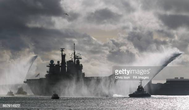Fire tugs spray jets of water into the air as HMS Illustrious returns to Portsmouth Royal Navy Base almost a month later than planned after being...