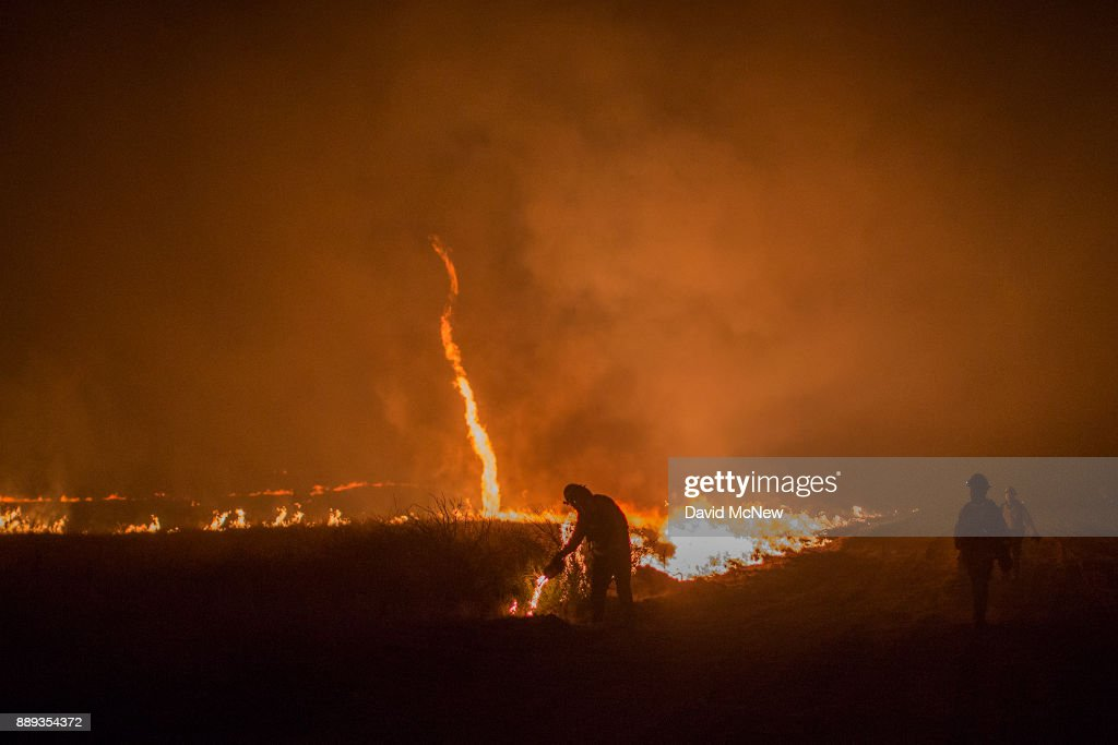 A fire whirl, also called a fire devil, forms as firefighters use drip torches to set a backfire at night in an effort to make progress against the Thomas Fire before the winds return with the daylight near Lake Casitas on December 9, 2017 near Ojai, California. Strong Santa Ana winds have been feeding major wildfires all week, destroying hundreds of houses and forcing tens of thousands of people to stay away from their homes.