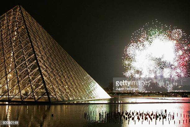 A fire work is shot in front of the Louvre Pyramid for the launch of the Fiac contemporary art fair of Paris at Cour Carree du Louvre on October 20...