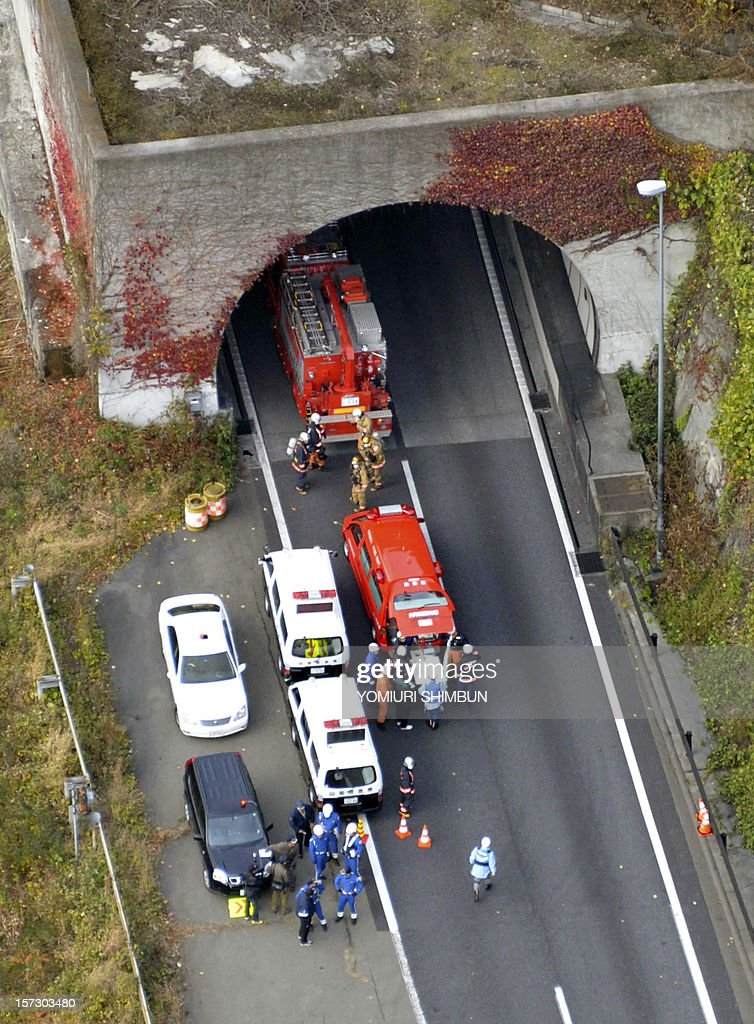 Fire workers prepare for their rescue operation outside the exit of the collapsed Sasago tunnel on the Chuo expressway in Otsuki city, Yamanashi prefecture, some 80-kilometre west of Tokyo on December 2, 2012. At least seven people are missing after concrete ceiling panels along a section of highway tunnel collapsed in Japan. The accident occurred on Tokyo-bound lanes inside the Sasago tunnel on the Chuo Expressway, some 80 kilometres (50 miles) west of the capital, at around 8:00 am on December 2, an official at the expressway traffic police said. ==JAPAN OUT== AFP PHOTO / YOMIURI SHIMBUN