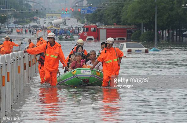 Fire workers transfer citizens with inflatable boat on flooded street on July 20 2016 in Taiyuan Shanxi Province of China Heavy rainstorm stroke west...