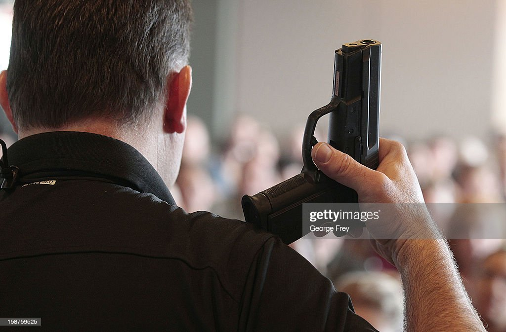 Firearm instructor Clark Aposhian holds a handgun up as he teaches a concealed-weapons training class to 200 Utah teachers on December 27, 2012 in West Valley City, Utah. The Utah Shooting Sports Council said it would waive its $50 fee for concealed-weapons training for Utah teachers.