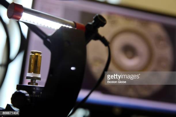 Firearms examiner Chris Finn uses a microscope to compare markings on cartridge casings in the Firearms Analysis Unit at Police Headquarters in...