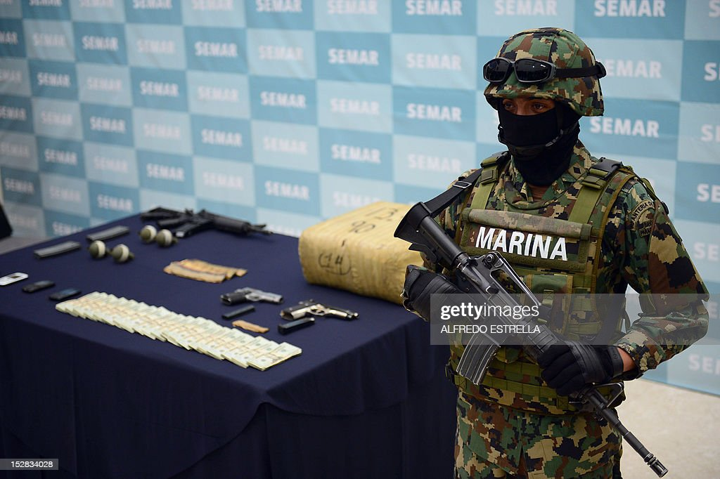 Firearms, hand grenades and other illegal stuff seized to Ivan Velazquez Caballero, aka 'Z 50' or 'El Taliban' (not framed), senior leader in the Zetas drug cartel and member of the Gulf cartel, during his presentation to the press at the Mexican Navy headquarters in Mexico City, on September 27, 2012. Velazquez Caballero was on a list of Mexico's most wanted drug traffickers, with an offer of some $2.3 million for information leading to his capture. AFP PHOTO/Alfredo Estrella