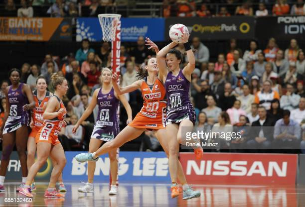 Firebirds Caitlyn Nevins catches the ball evading Giants Bec Bulley during the round 13 Super Netball match between the Giants and the Firebirds at...