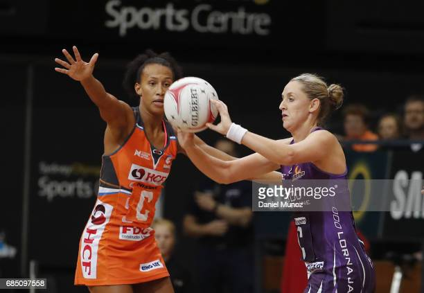 Firebirds Erin Burger passes the ball evading Giants centre Serena Guthrie during the round 13 Super Netball match between the Giants and the...