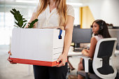 Fired female employee holding box of belongings in an office