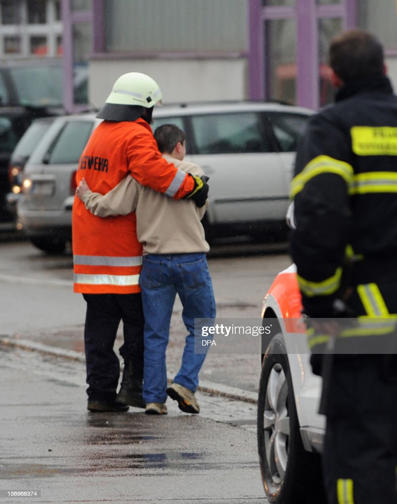 A firefighter accompanies a boy in front of house with a workshop for handicapped people in Titisee- Neustadt, southern Germany on November 26, 2012. Fourteen people died after a fire broke out.