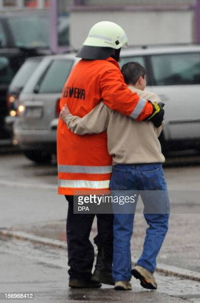 A firefighter accompanies a boy in front of house with a workshop for handicapped people in Titisee Neustadt southern Germany on November 26 2012...