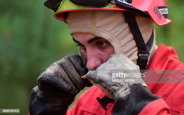 A firefighter adjusts the hood while combatting a wildfire in Vale da Ponte Pedrograo Grande on June 20 2017 The huge forest fire that erupted on...