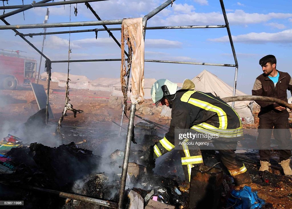 Firefighter and a civilian extinguish fire after a Syrian regime warcraft targeted the Kamuna refugee camp near the Sarmada town of Idlib province, Syria on May 05, 2016. Eight people were killed and another 30 injured when a regime warcraft targeted the Kamuna refugee camp.