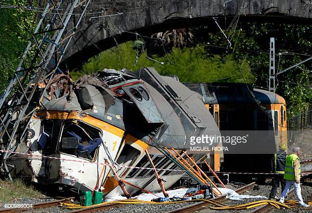 A firefighter and a man stand past the wreckage of a train that derailed in O Porrino northwestern Spain leaving at least four people dead and some...